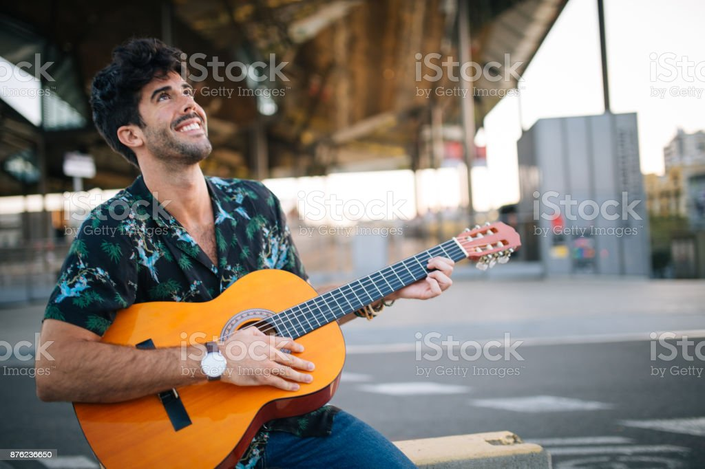 Guy playing acoustic guitar stock photo