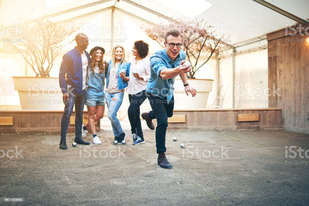 Guy playing petanque indoors with friends stock photo