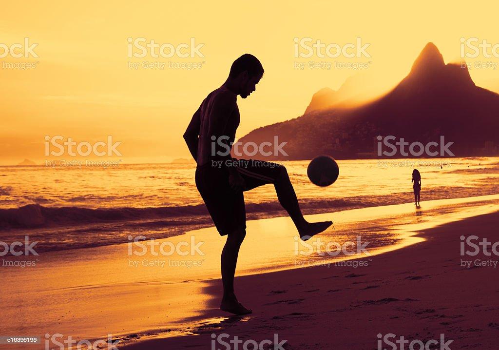 Guy playing soccer at beach at Rio at sunset stock photo
