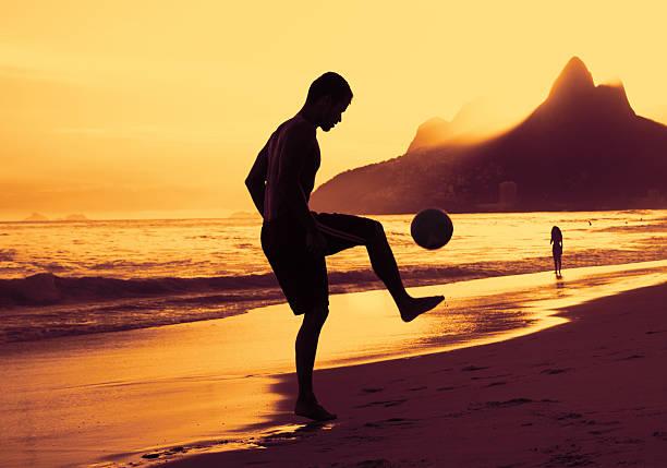 menino jogando futebol na praia no rio ao pôr-do-sol - futebol de areia - fotografias e filmes do acervo