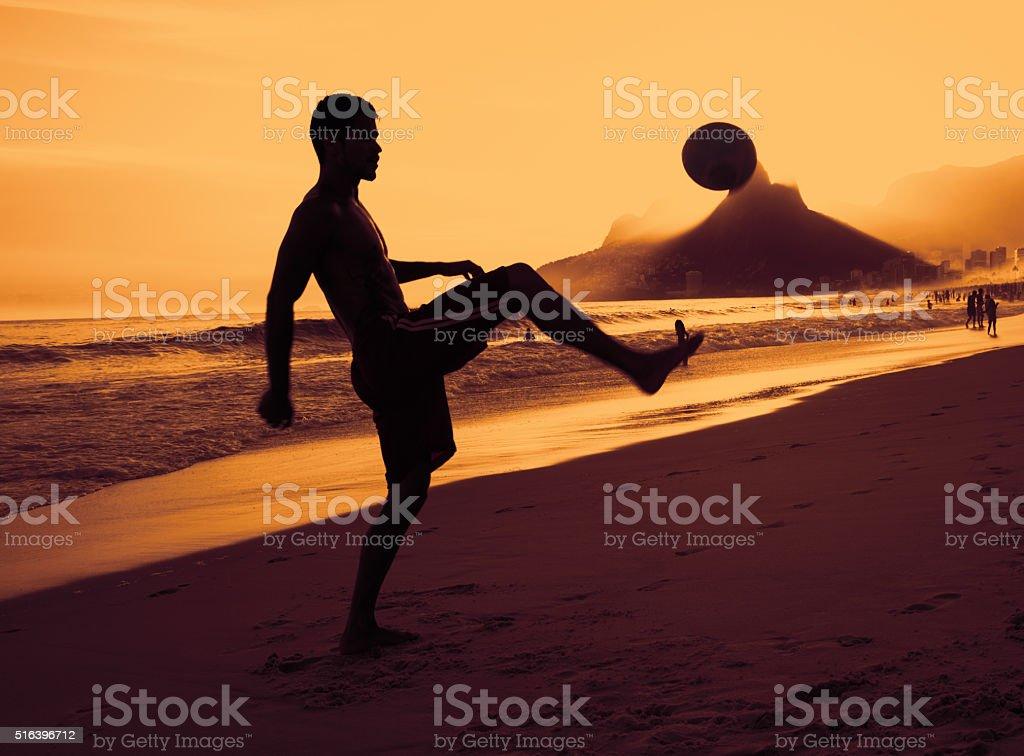 Guy playing soccer at beach at Rio de Janeiro stock photo