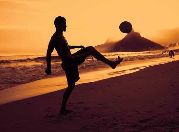 menino jogando futebol na praia no rio de janeiro - futebol de areia - fotografias e filmes do acervo