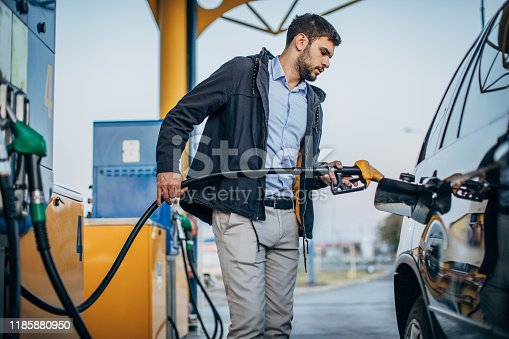 One man, pouring gasoline in his car at the gas station.