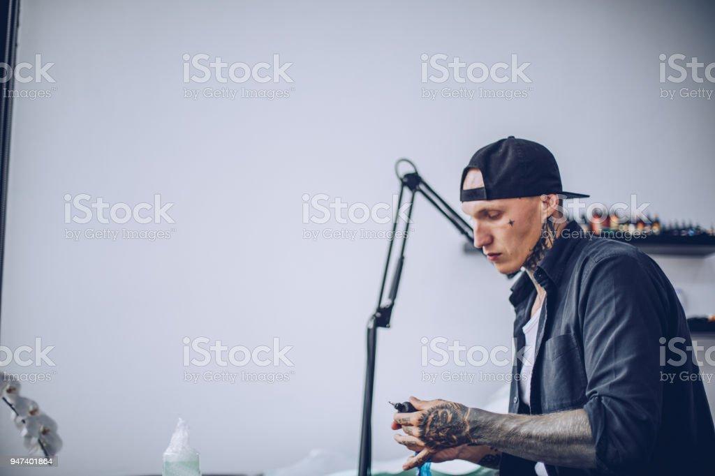 Guy preparing tattoo machine for work stock photo