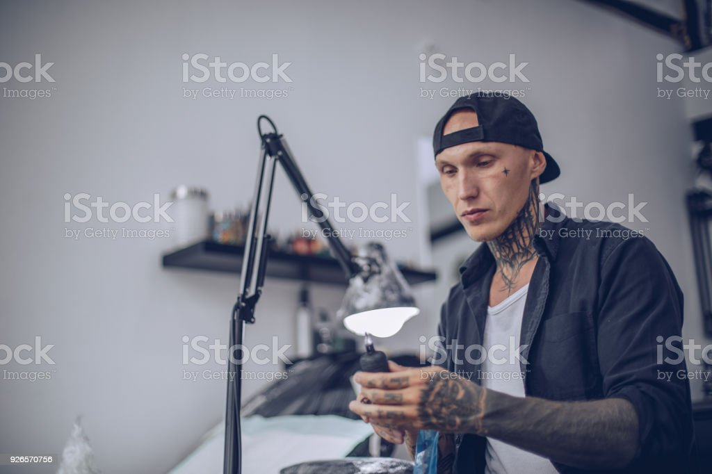 Guy preparing tattoo machine stock photo
