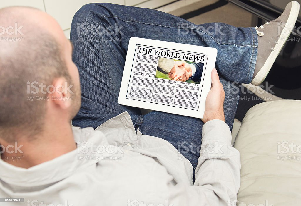 Guy reading a newspaper on digital tablet royalty-free stock photo