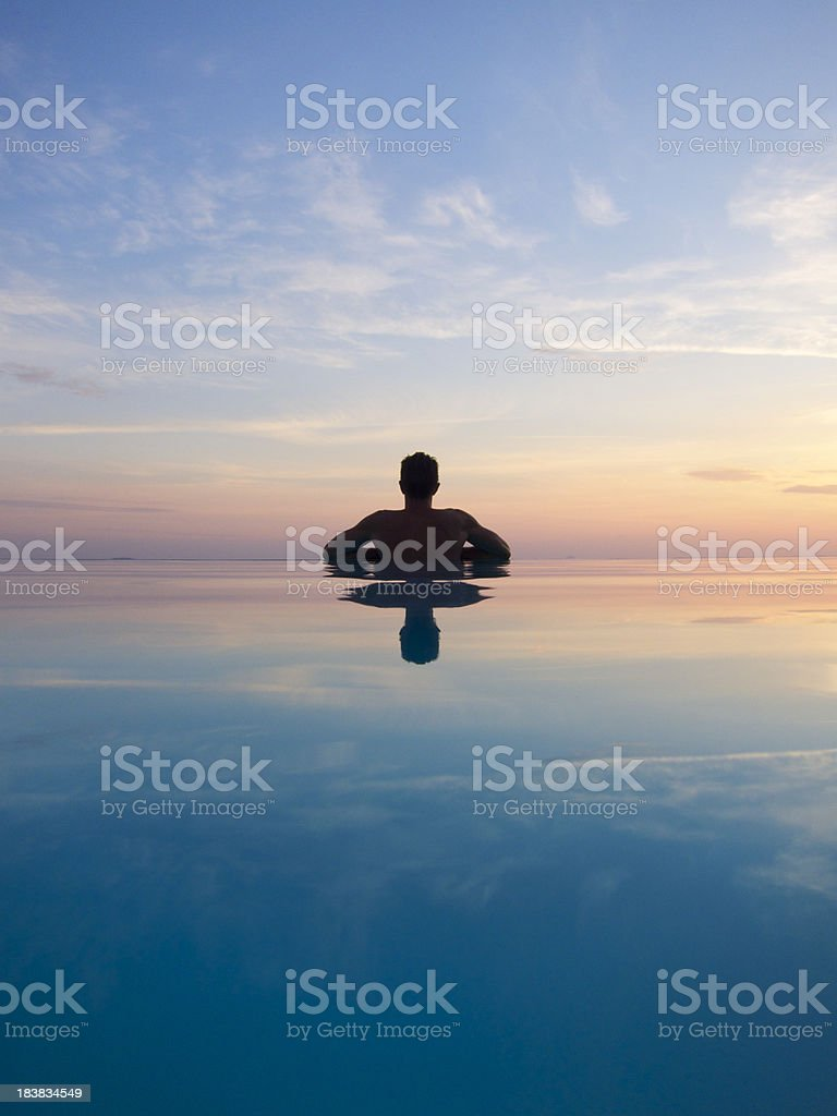 Guy Reflects in Silhouette on Sunset Infinity Pool royalty-free stock photo