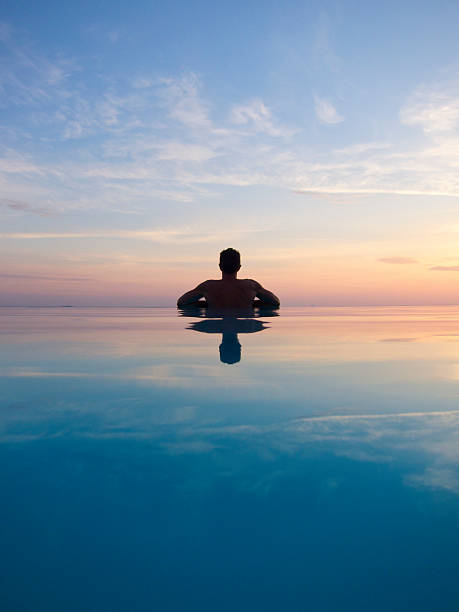 """Guy Reflects in Silhouette on Sunset Infinity Pool """"Guy rests at the edge of an infinity pool, reflecting in silhouette with sunset sky"""" infinity pool stock pictures, royalty-free photos & images"""