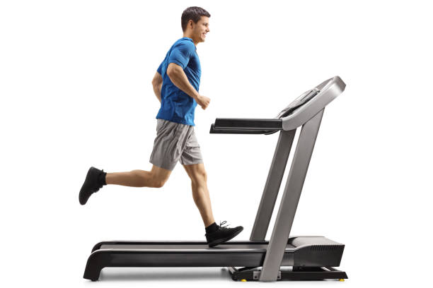 Guy running on a treadmill Full length profile shot of a guy running on a treadmill isolated on white background treadmill stock pictures, royalty-free photos & images