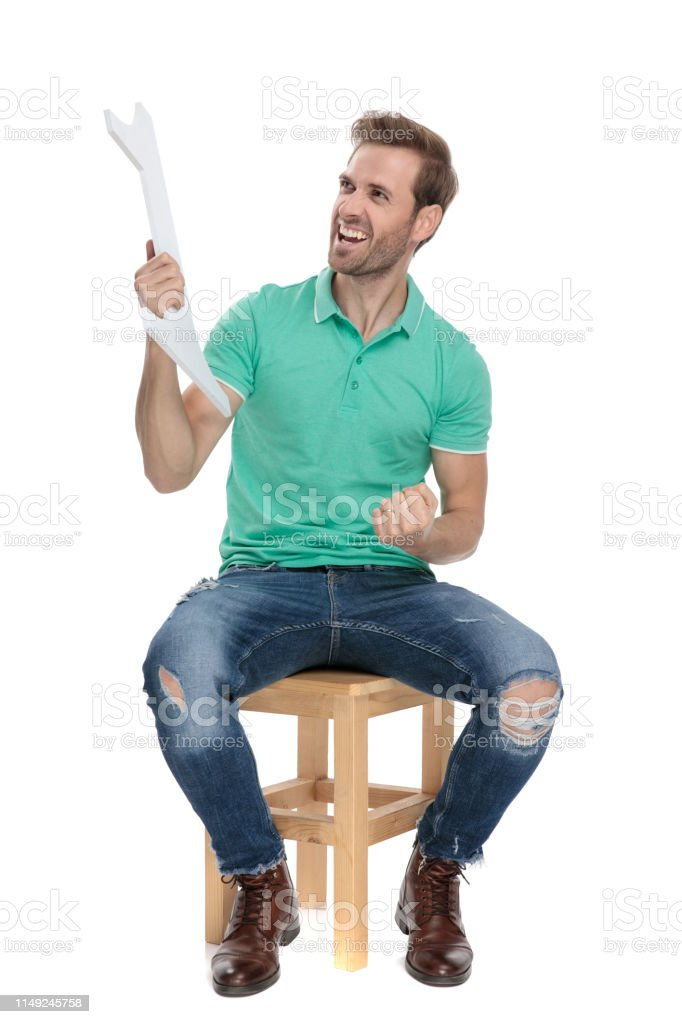 guy screaming with number one sign in hand while sitting stock photo
