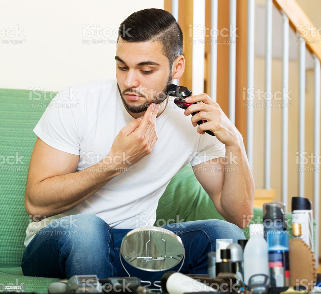 guy shaving by electric shaver stock photo