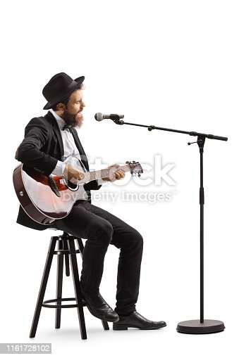 Full length shot of a guy singing on a microphone and playing an acoustic guitar isolated on white background