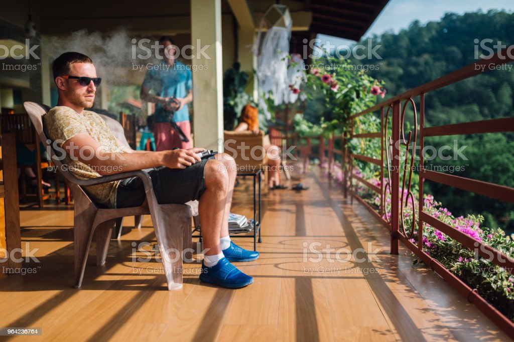 guy sits on a terrace in the highlands and smokes an electronic cigarette stock photo