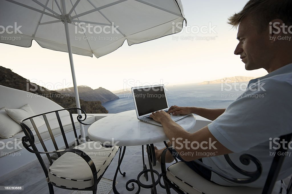 Guy Sits Typing on Patio Overlooking Dramatic Sea Scene stock photo