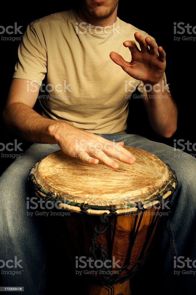 Guy sitting down and playing on a drum stock photo