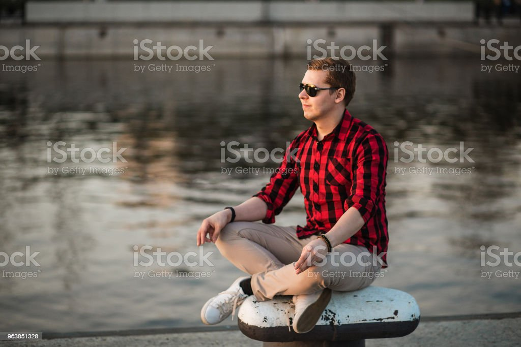 Guy sitting in the lotus position in city embankment and looking at the setting sun - Royalty-free Adult Stock Photo