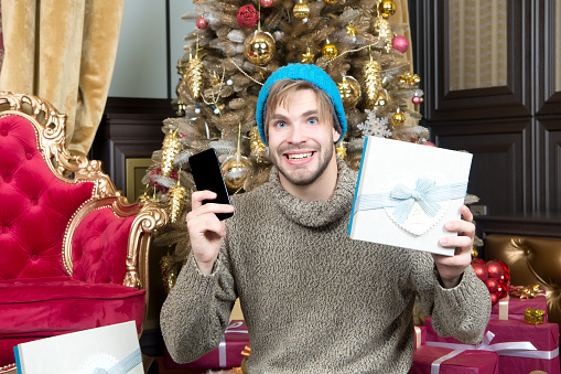 Guy smile with mobile phone at xmas tree