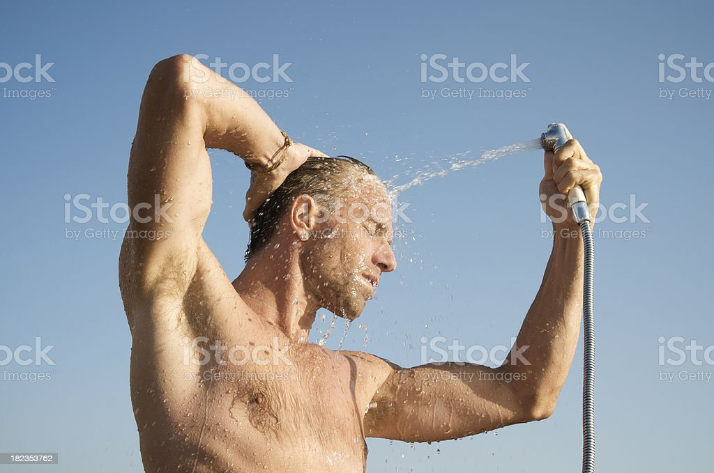 Guy Sprays Himself w Water in the Sun royalty-free stock photo