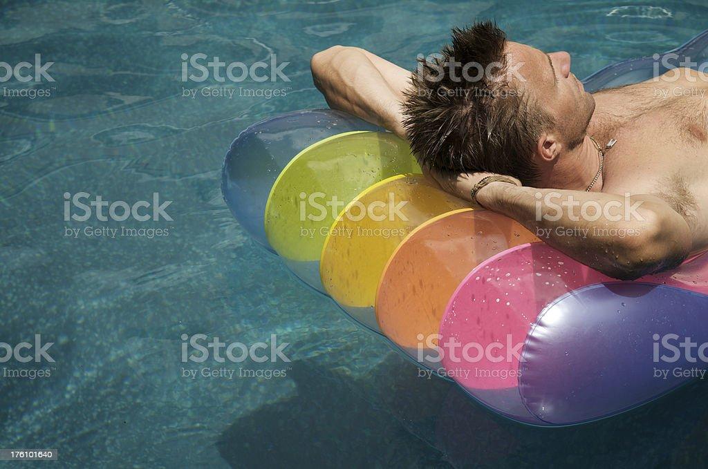 Guy Sunbathes on Colorful Pool Raft royalty-free stock photo