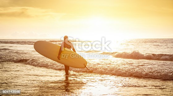 istock Guy surfer walking with surfboard at sunset in Tenerife - Surf long board training practitioner in action - Sport travel concept with sof focus water near feet - Warm sunshine color foltered tones 924143546