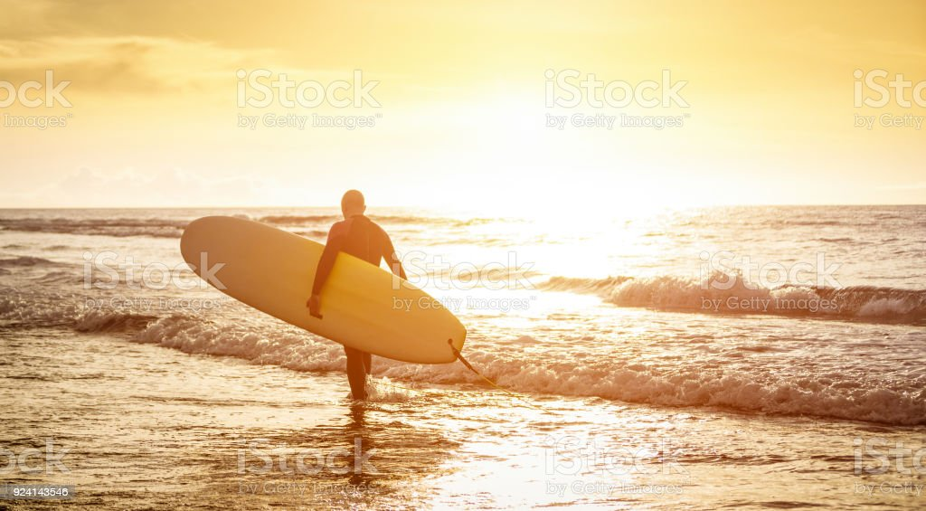 Guy surfer walking with surfboard at sunset in Tenerife - Surf long board training practitioner in action - Sport travel concept with sof focus water near feet - Warm sunshine color foltered tones stock photo