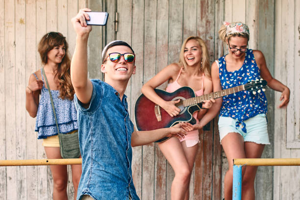 guy takes selfie with front camera while hanging out with friends - concert selfie stock photos and pictures