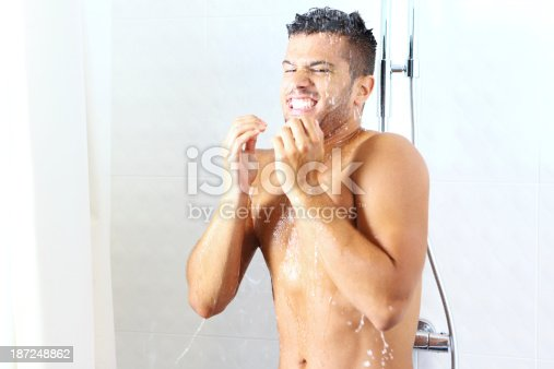 Young caucasian man under a cold morning shower.He expected hot water but something went wrong that morning. His body is shivering.