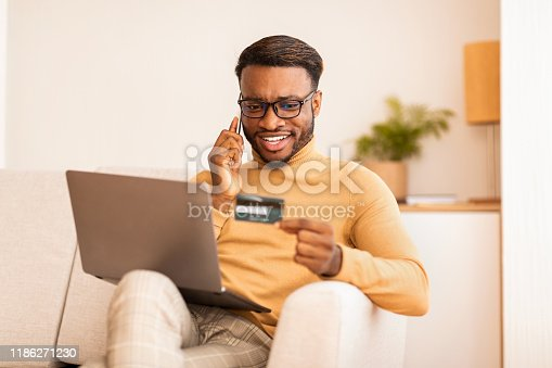 1173546354 istock photo Guy talking on phone shopping online sitting on couch indoor 1186271230