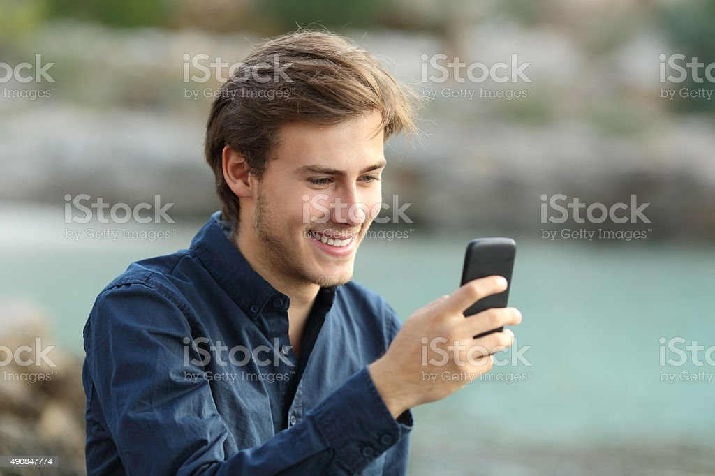 Guy texting on the phone on the beach stock photo