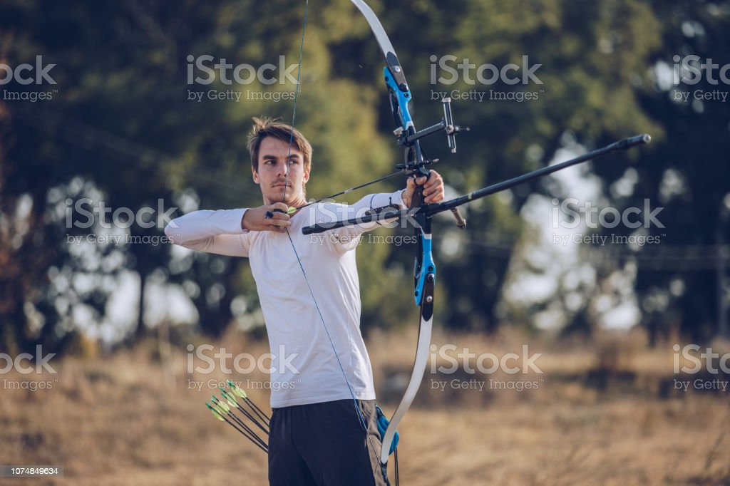 One man, young archer with bow and arrow training alone outdoors in...