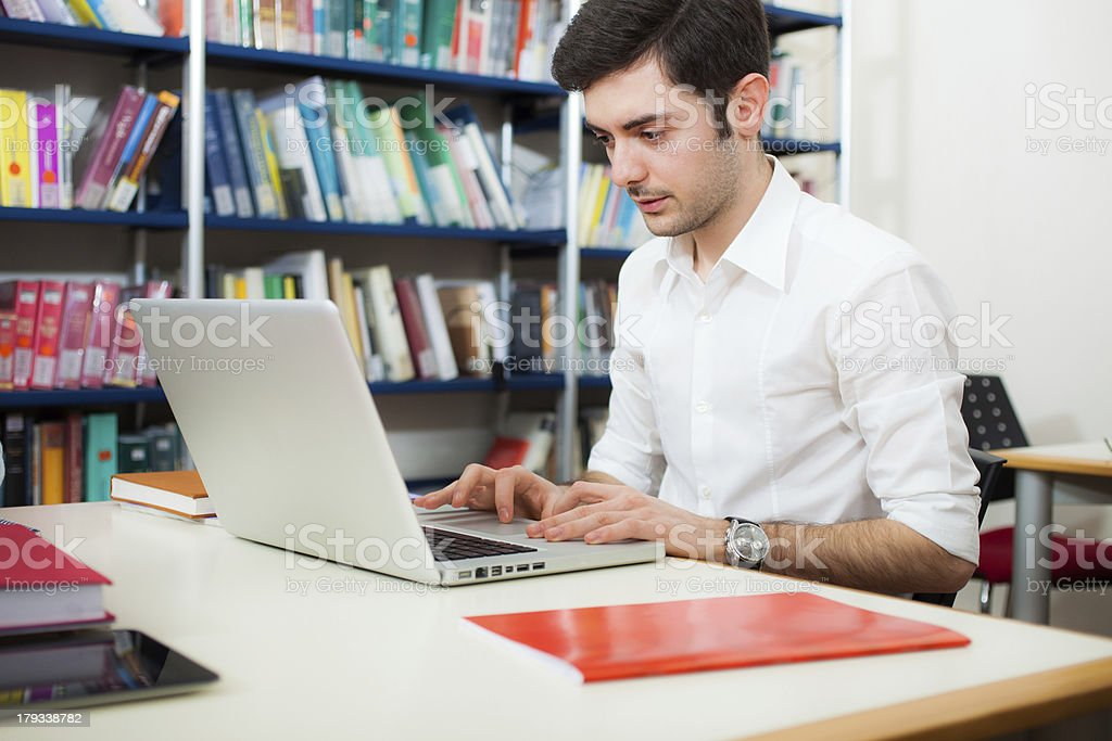 Guy using his laptop in a library royalty-free stock photo