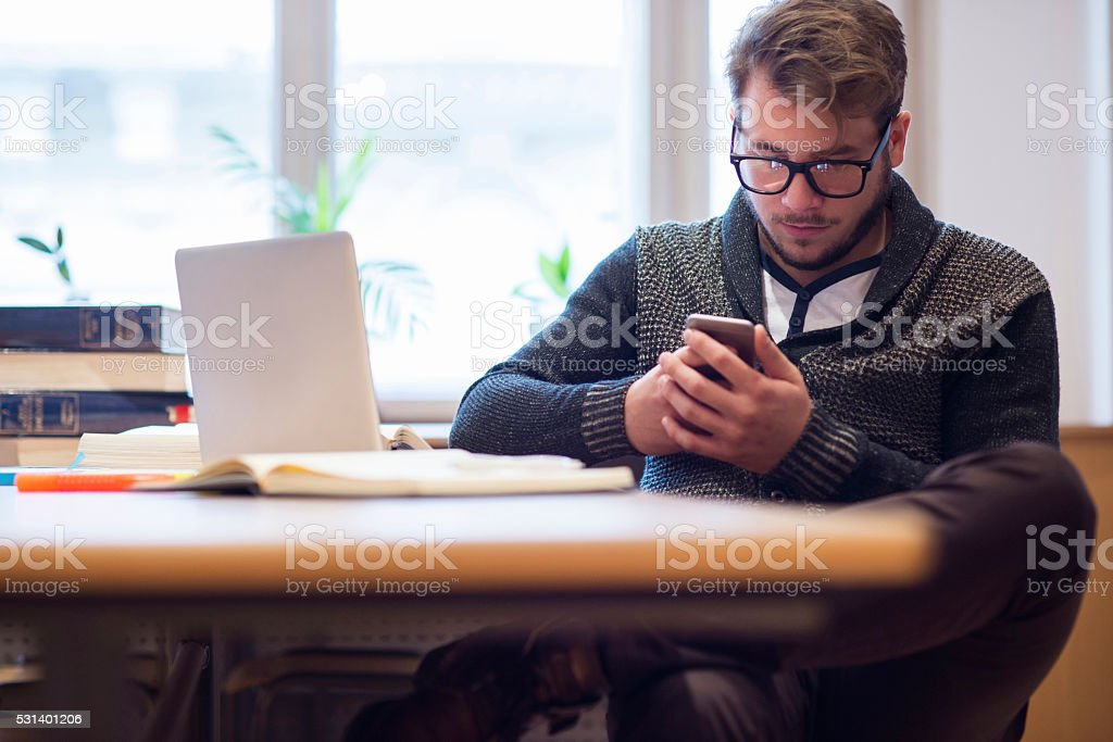 Guy using smartphone and laptop stock photo