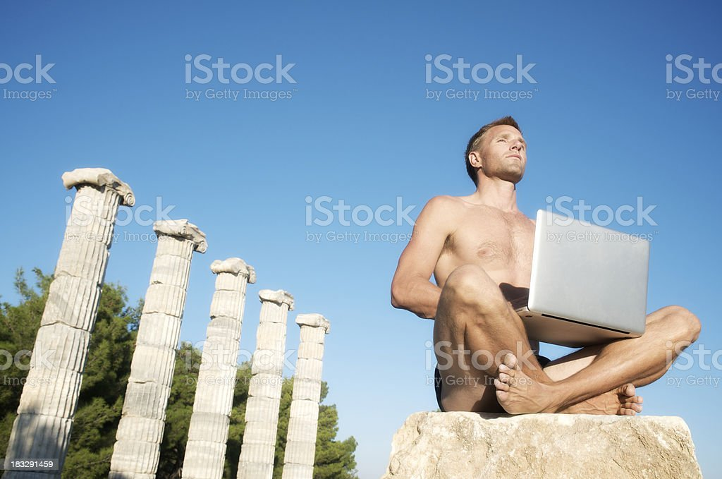 Guy w Laptop Sits Next to Row of Ancient Columns stock photo