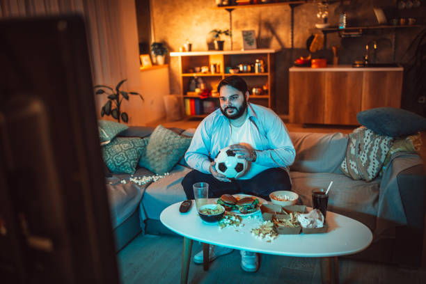 Guy watching a soccer match One man, sitting at home, eating burgers and watching a sports match alone. man cave couch stock pictures, royalty-free photos & images