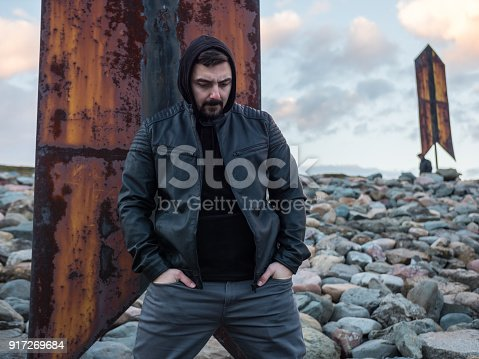 836798276 istock photo Guy wearing a hood and leather jacket standing outdoors contemplating 917269684