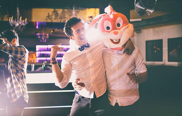 Guy usa bunny cabeza con amigos en la fiesta en club - foto de stock