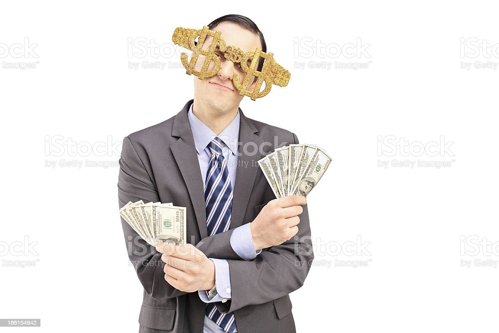 Guy wearing dollar sign glasses and holding dollars royalty-free stock photo