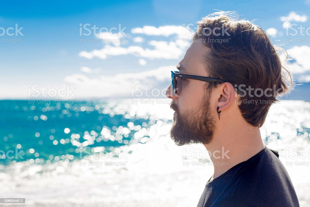 Guy with beard and sunglasses at beach looking sideways royalty-free stock photo