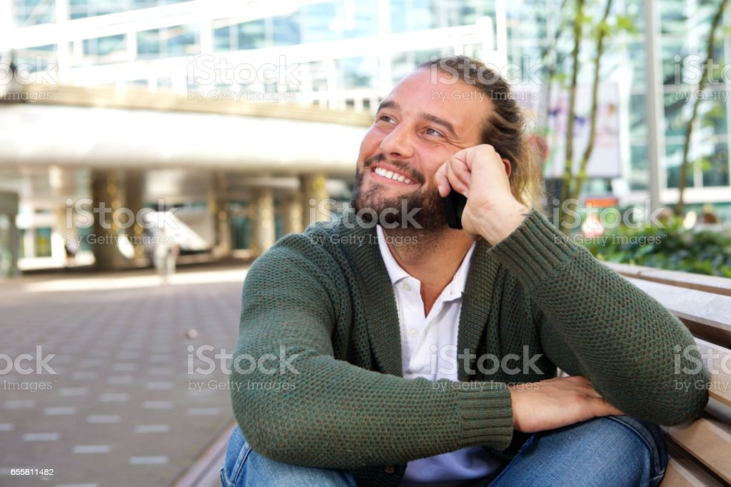 Guy with beard sitting on bench in the city with mobile phone stock photo