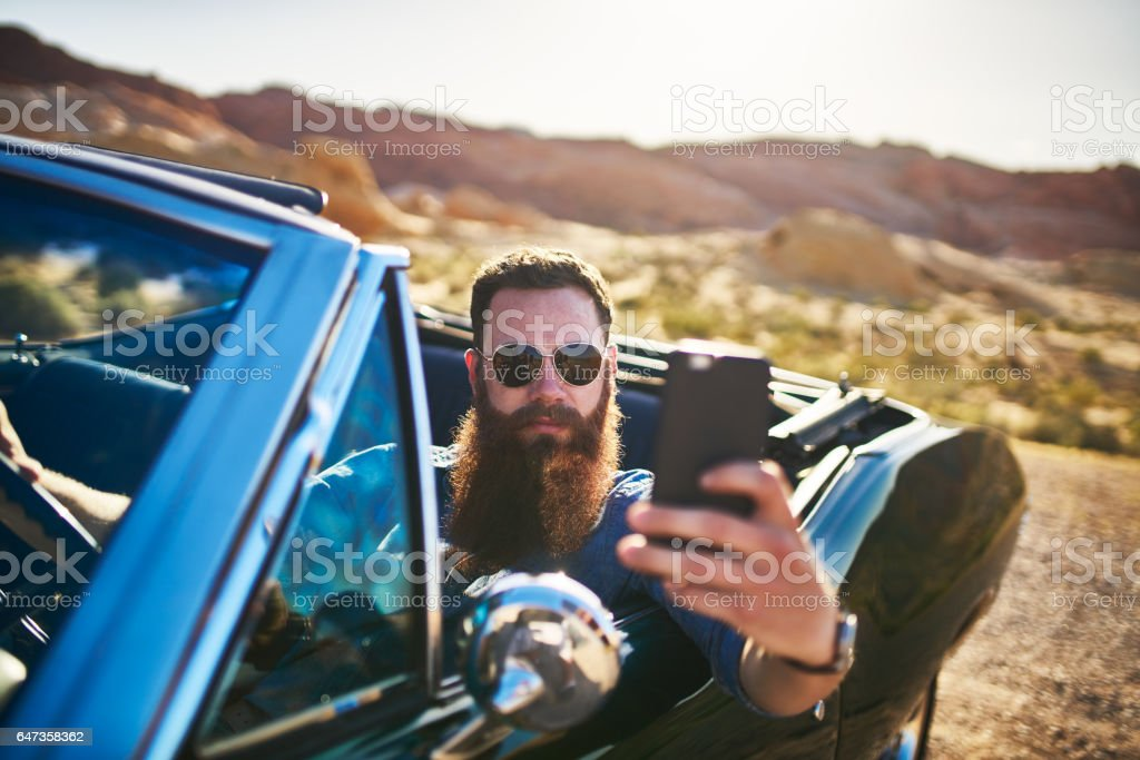 guy with beard taking selfie in vintage car showing off stock photo
