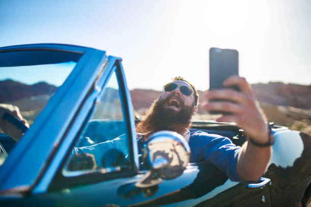 guy with beard taking selfie in vintage car showing off - Photo