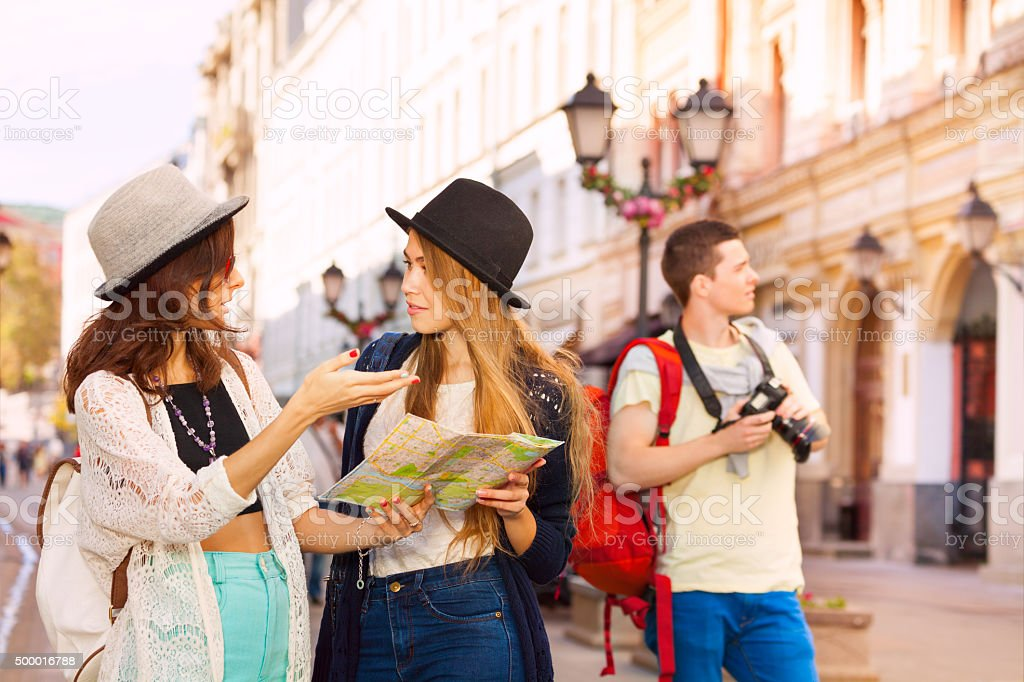 Guy with camera and two women together as tourists stock photo