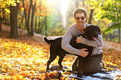 guy with dog labrodor in autumn park at sunset