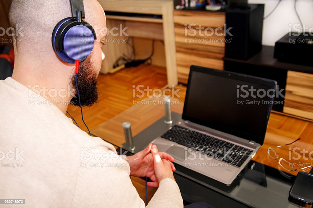 Guy with headphones listening music on laptop in living room - foto de acervo