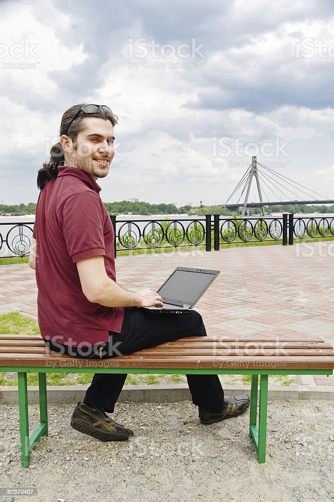 Guy with laptop in the park royalty-free stock photo