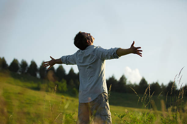 guy mit outstreched armen stehen in einem meadow - gott sei dank stock-fotos und bilder