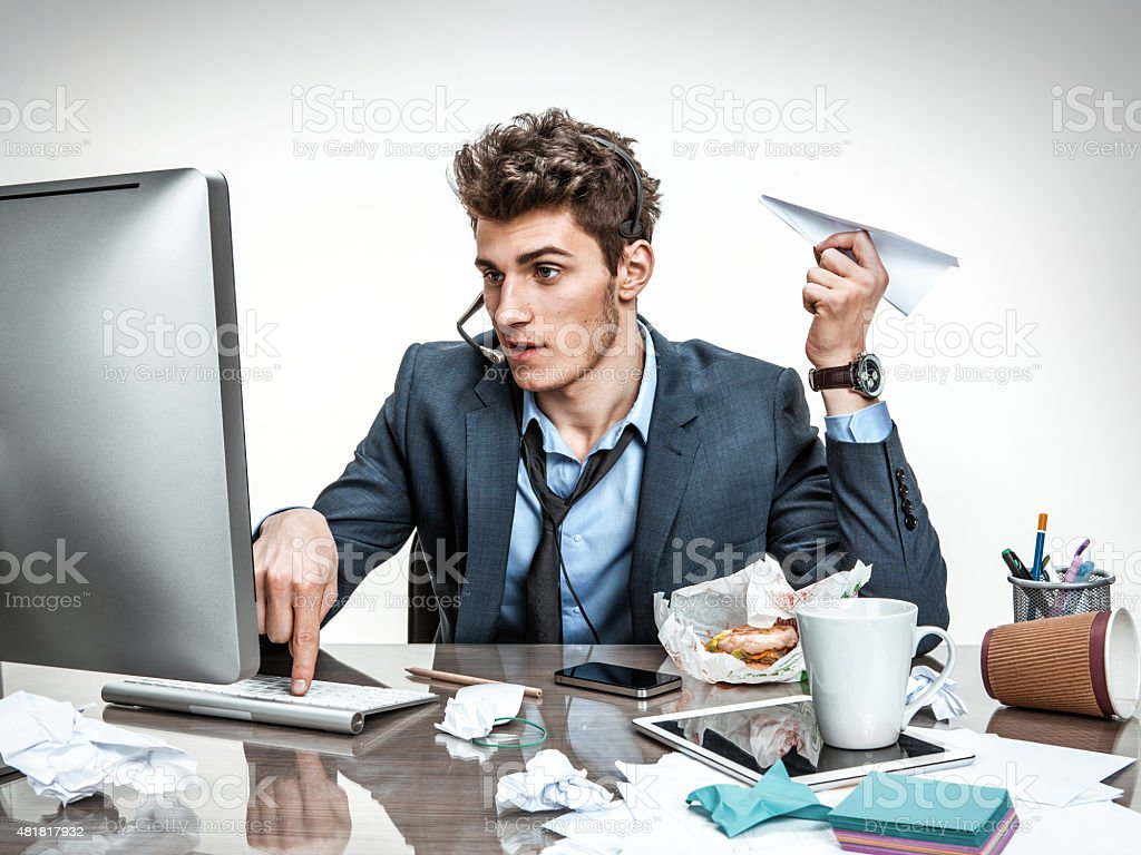 Guy with paper plane typing on a computer stock photo