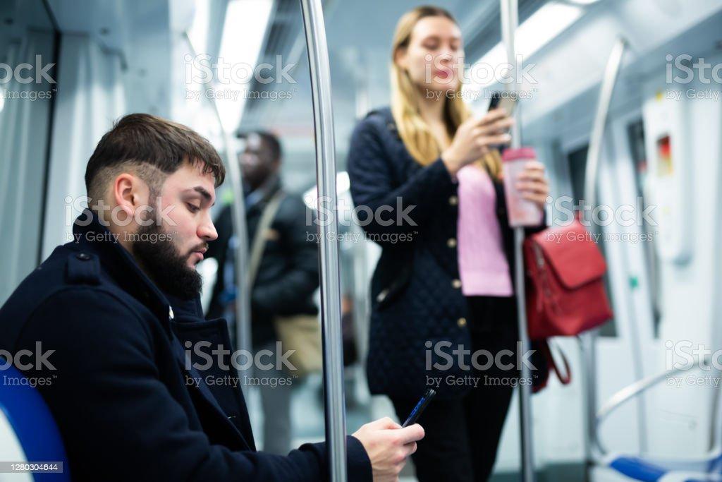 Tipo con teléfono sentado en el va coche subterráneo - Foto de stock de 20-24 años libre de derechos