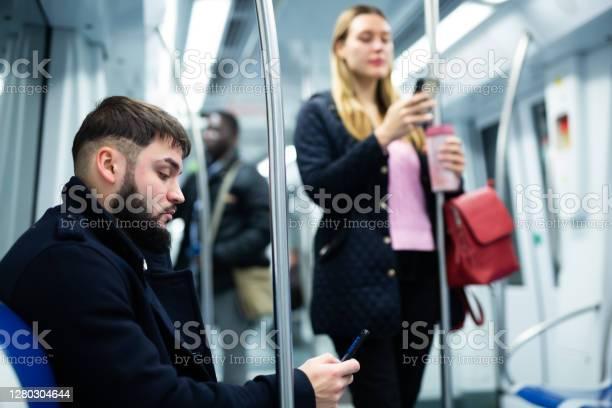 Tipo Con Teléfono Sentado En El Va Coche Subterráneo Foto de stock y más banco de imágenes de 20-24 años
