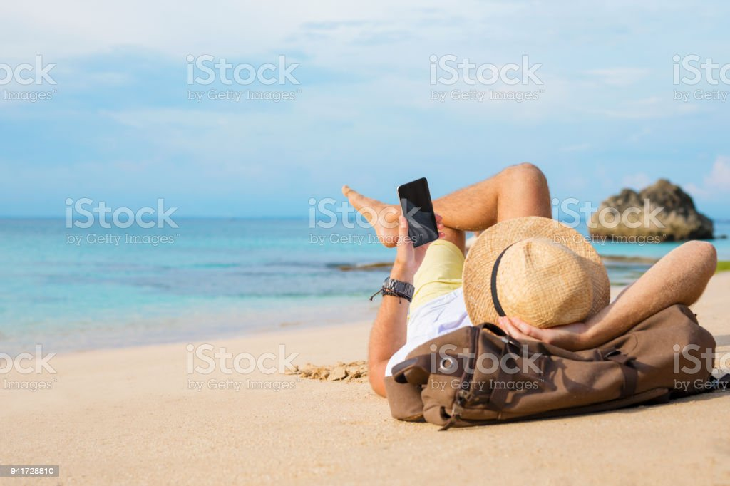 Guy with smartphone lying on the beach stock photo